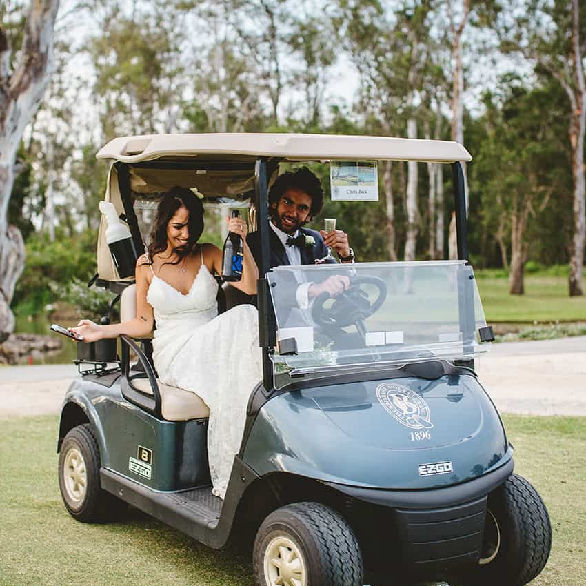 Bride and groom with champagne on the golf course