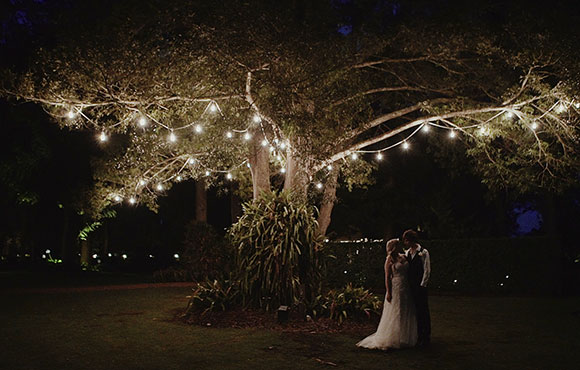 Married couple under a fairy-lit tree
