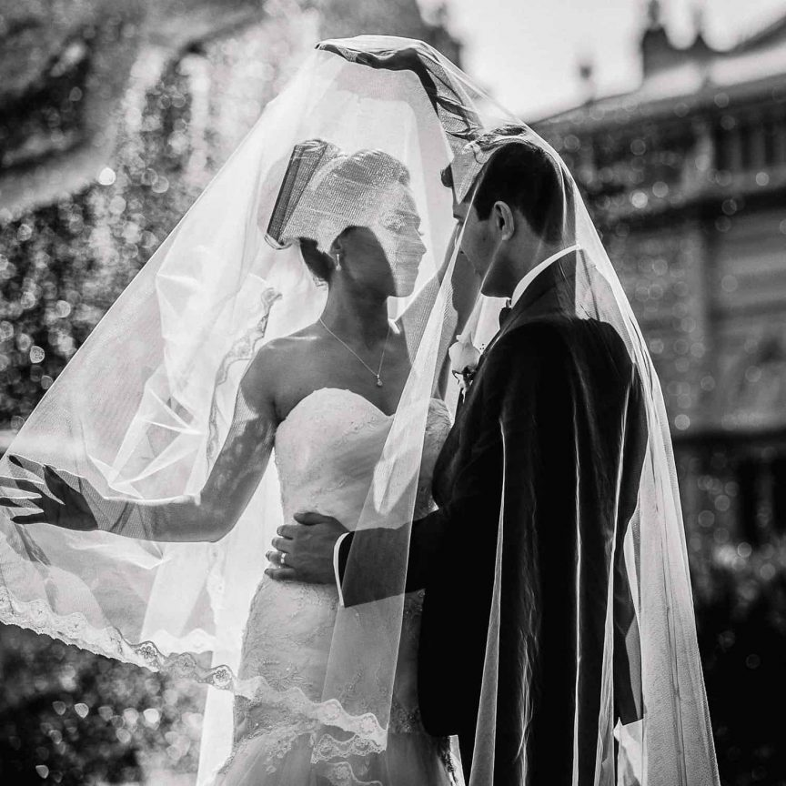 Bride and groom under veil in black and white