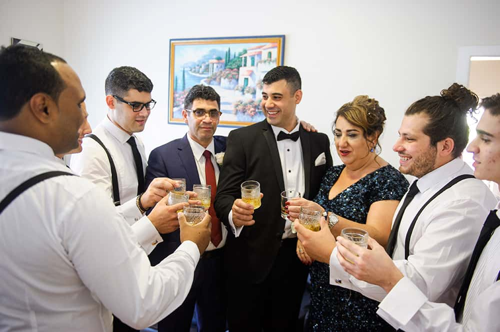 Groom, his groomsmen and parents before the wedding