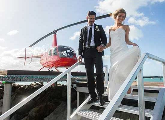 Wedding couple walking from their private helicopter transport
