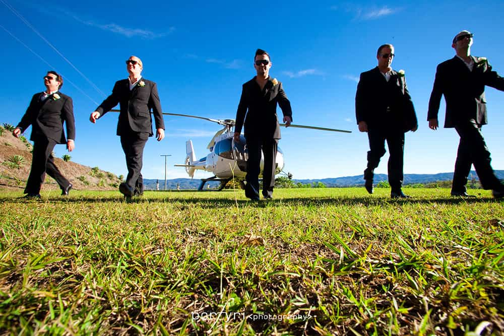 Groom and groomsmen walking from helicopter at Glengariff Historic Estate.