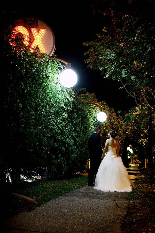 Bride and groom walking through the Golden Ox's gardens at their Redcliffe wedding.