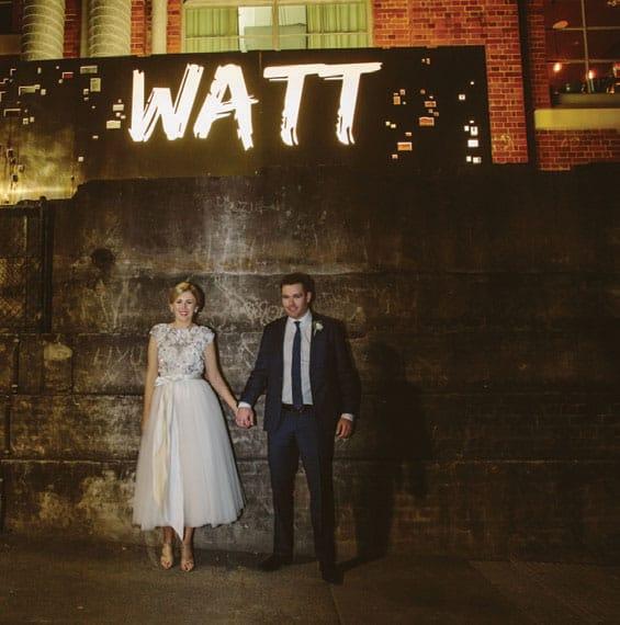 Bride and groom under light-up signage