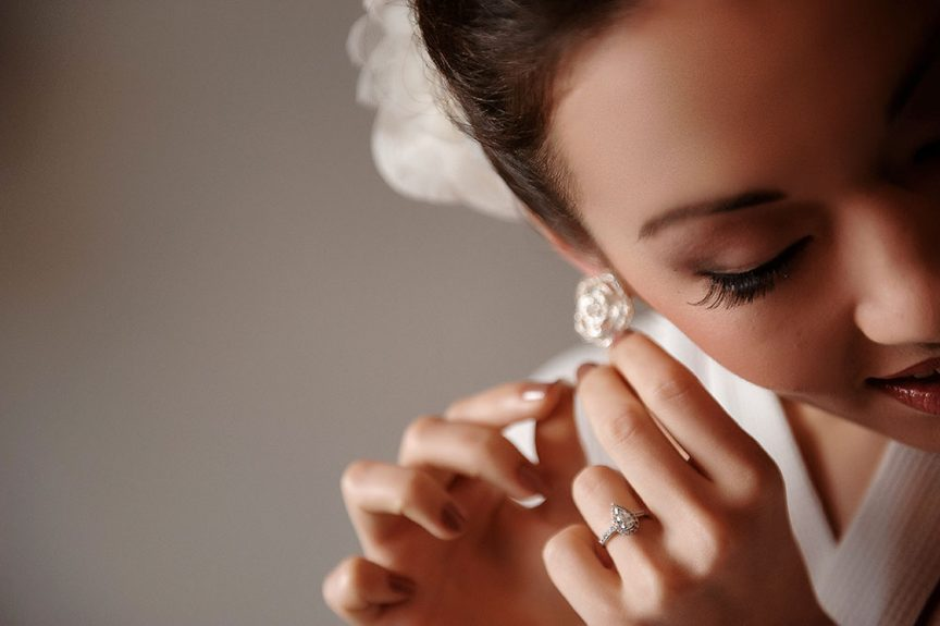 beautiful bride putting on earings