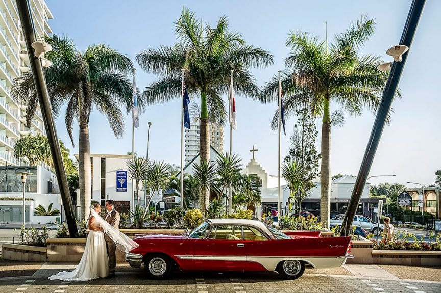 wedding couple with red car by Christopher Thomas Photography