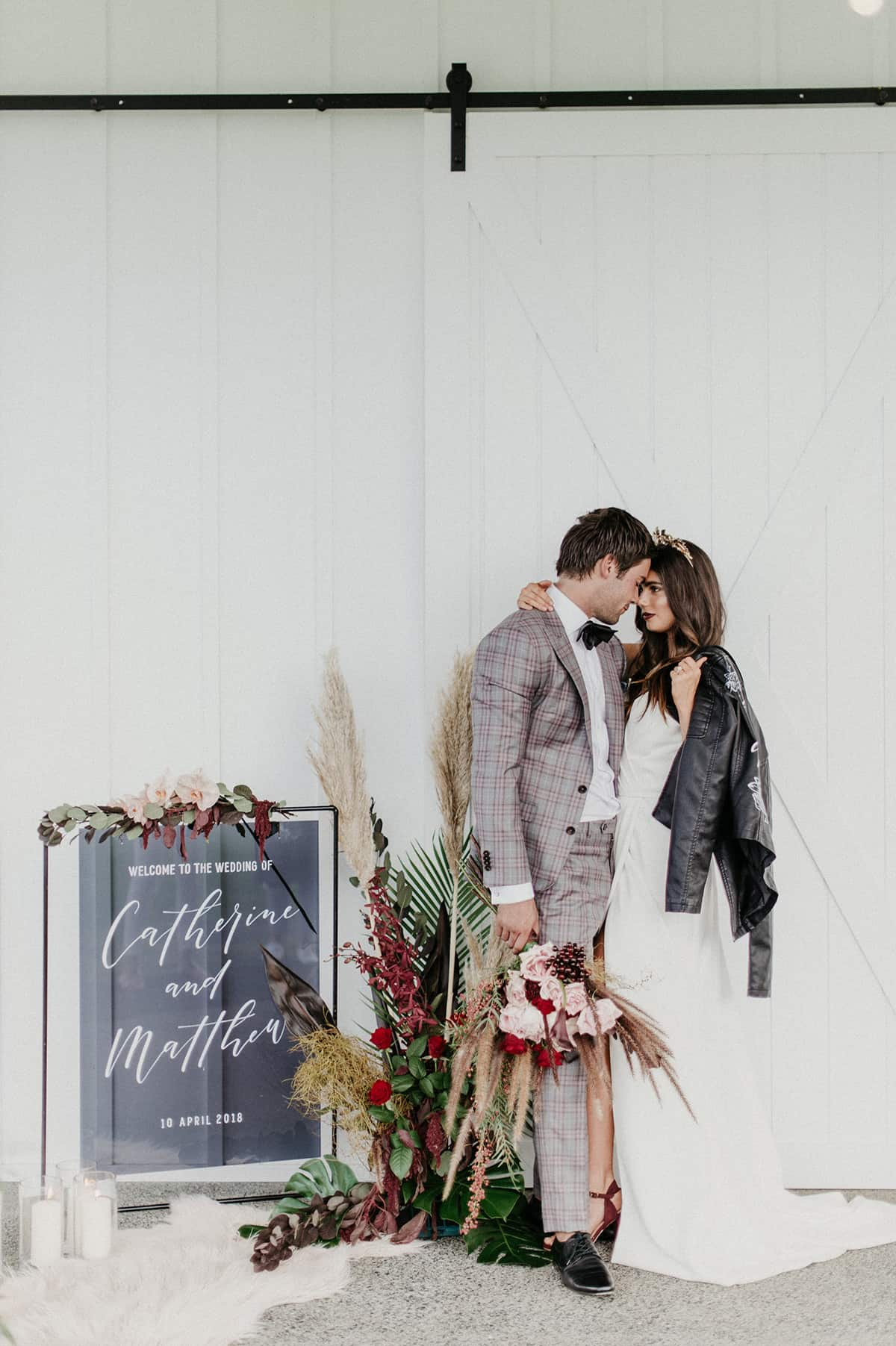 bride and groom with wedding sign