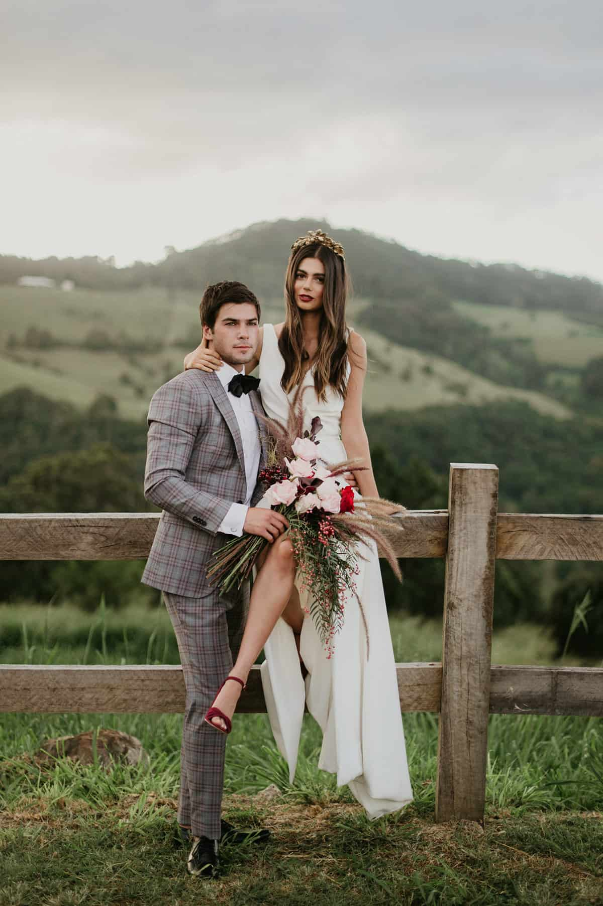 bride and groom sitting on country fence