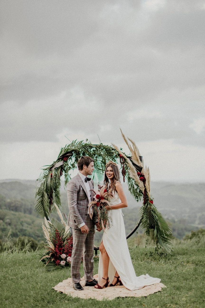 wedding couple with ceremony arbour
