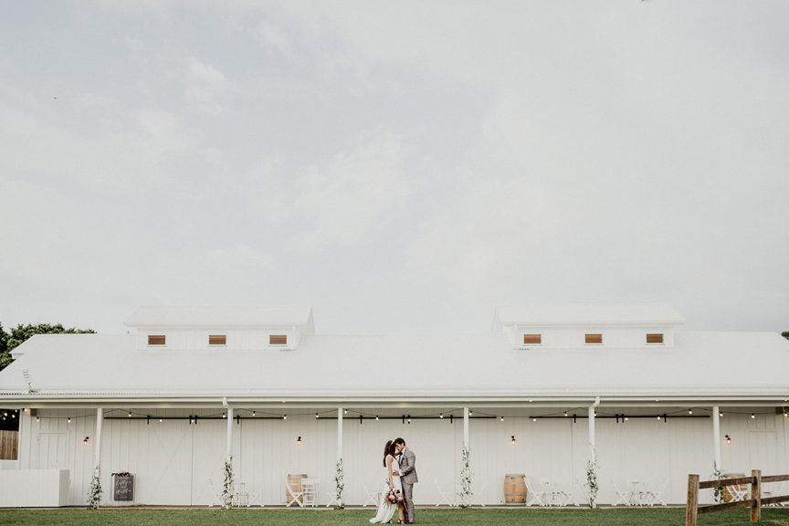 bride and groom out front of wedding barn