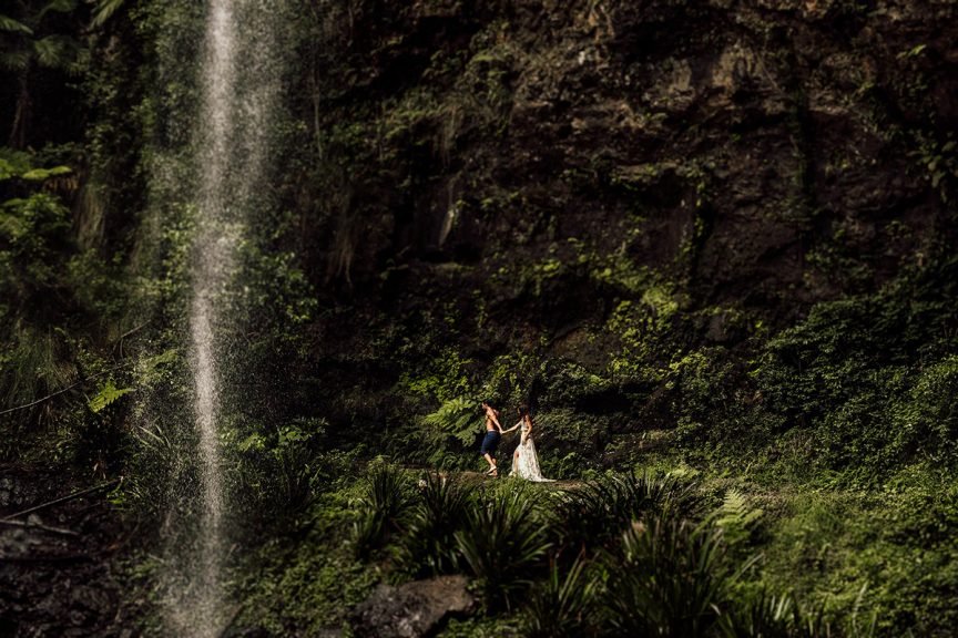 Couple walking past waterfall