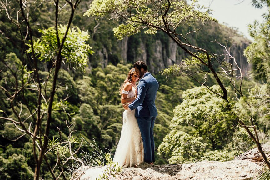 Couple embracing on rock outlook in rainforest