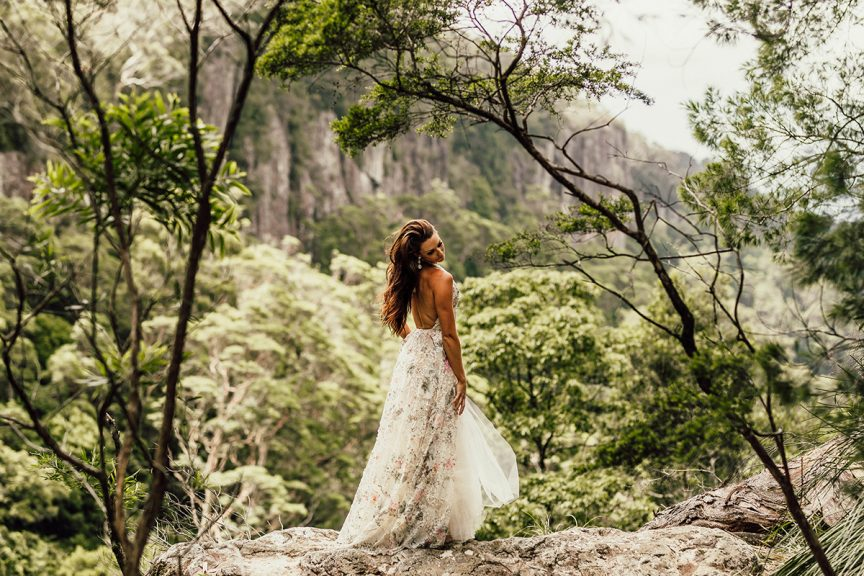 Bride on rock outlook in rainforest