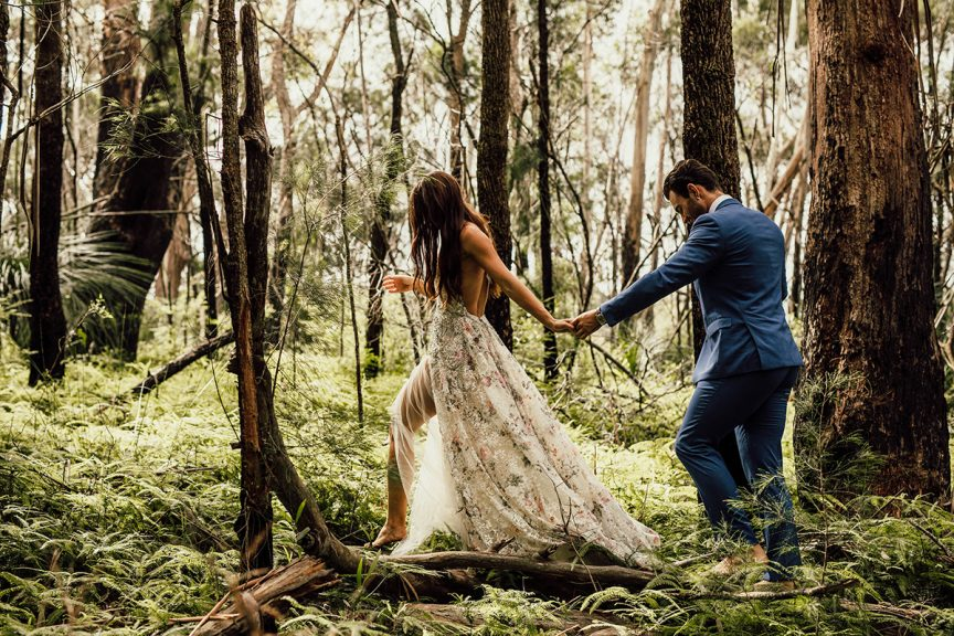 Bride leading groom in rainforest