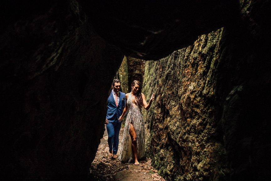 Couple walking near rock formation in rainforest