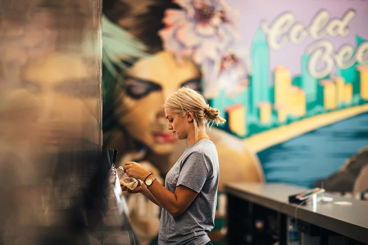 Brew-Baby---Balter-Brewery-girl-behind-bar-with-mural